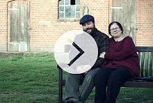 Vorschaubild für Video mit Play-Button: Mann und Frau auf Holzbank vor Backstein-Schuppen