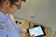 Christoph Kniehase schaut auf sein Tablet mit dem geöffneten Energiesparkonto.