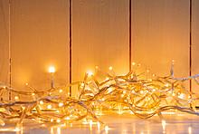 Weihnachtsbeleuchtung: gelb strahlende Lichterkette auf einem weißen Fußboden vor einer weiß getäftelten Wand