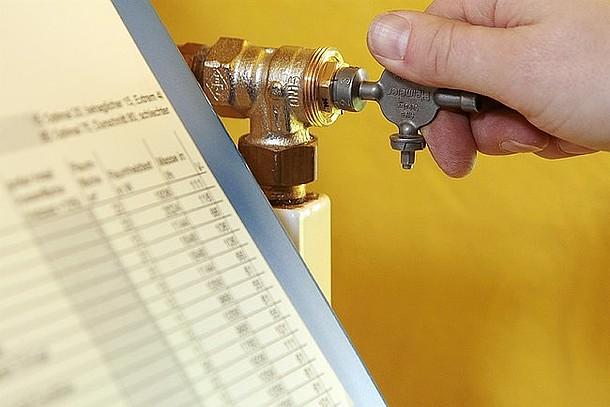 Ein Handwerker nimmt einen hydraulischen Abgleich vor und stellt die Heizungsthermostate richtig ein.