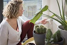 Thermostat einstellen: Eine Frau stellt das Heizungsthermostat am Hezkörper ein.