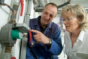 Handwerker erklärt Frau eine Pumpe