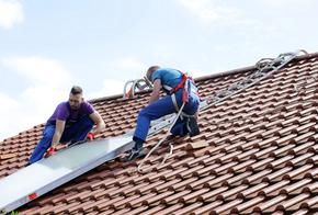 Installation Solarthermie: Männer schieben Kollektor übers Dach