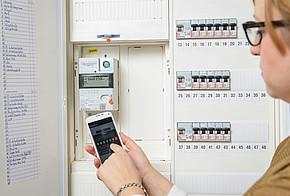 Smart Meter selbst gemacht: Eine Frau liest ihren Stromzählerstand ab und gibt ihn per App ins Energiesparkonto ein.
