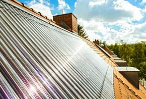 Röhrenkollektor auf Hausdach mit Sonnenreflektion